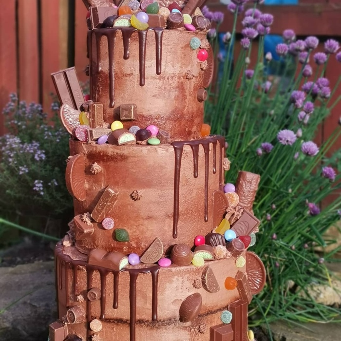 A three tiered chocolate cake dripped with chocolate ganache and loaded with sweets and chocolate treats