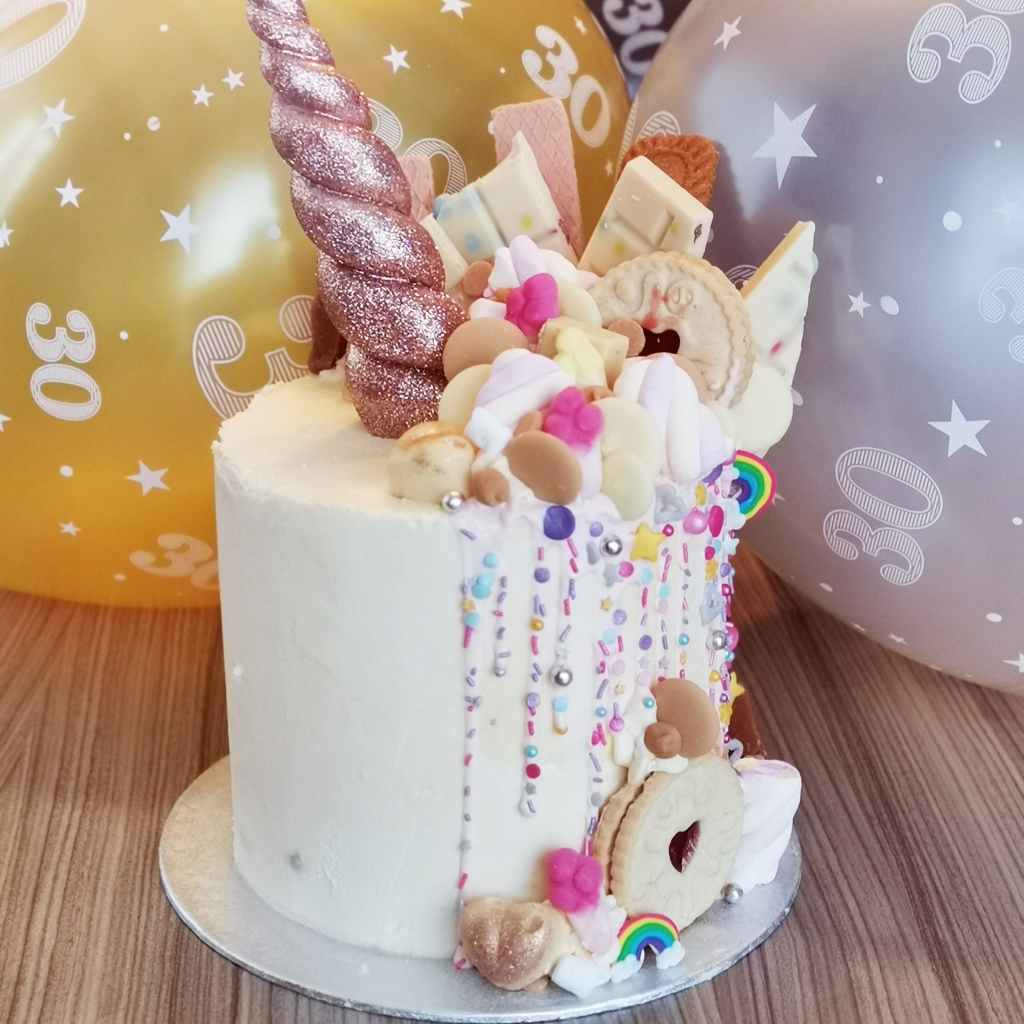 A cake with chocolate drips with a unicorn horn, loaded with sweets, chocolate and biscuits