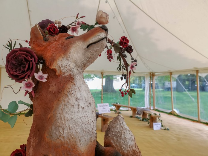 A close up photo of a 3D sculpted fox cake with a floral crown