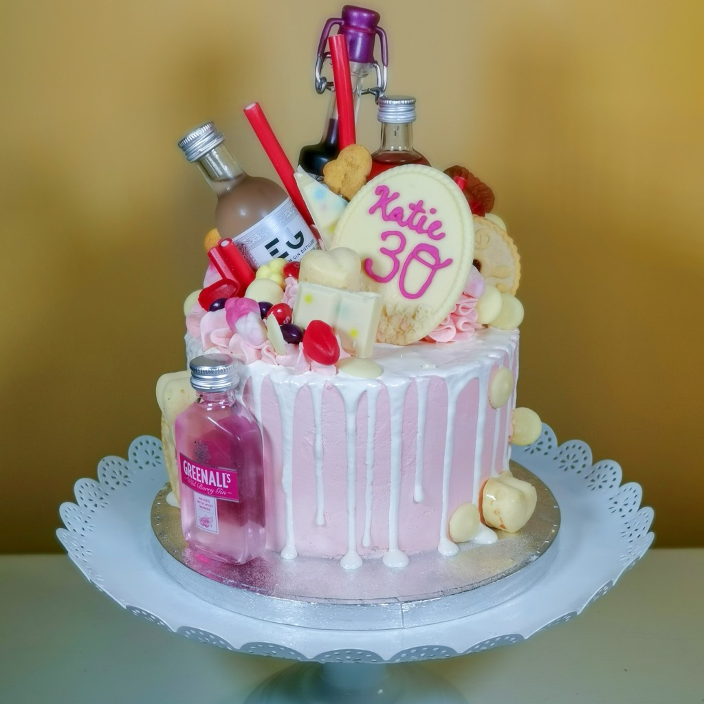 A cake loaded with miniature bottles of pink gin decorated with a chocolate drips, sweets and chocolate
